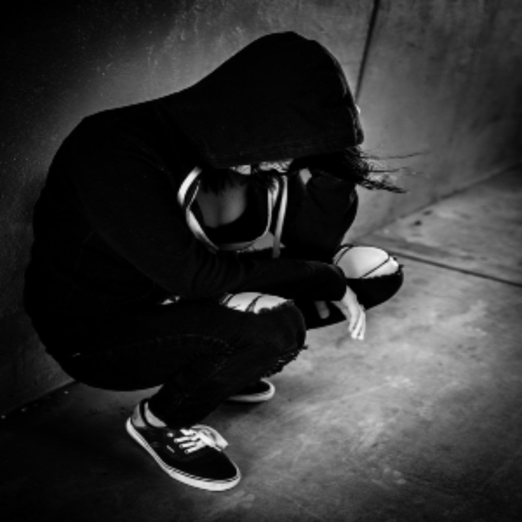 A woman crouching down with a hood on, looking at the floor.