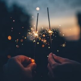 Two hands holding sparklers in the sunset